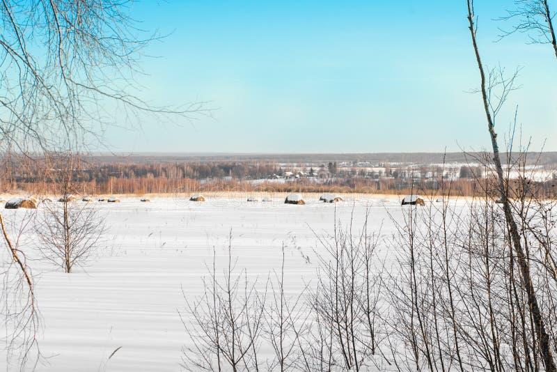 Τοπίο χειμερινής επαρχίας με τις χιονισμένες θυμωνιές χόρτου στον τομέα στοκ εικόνες