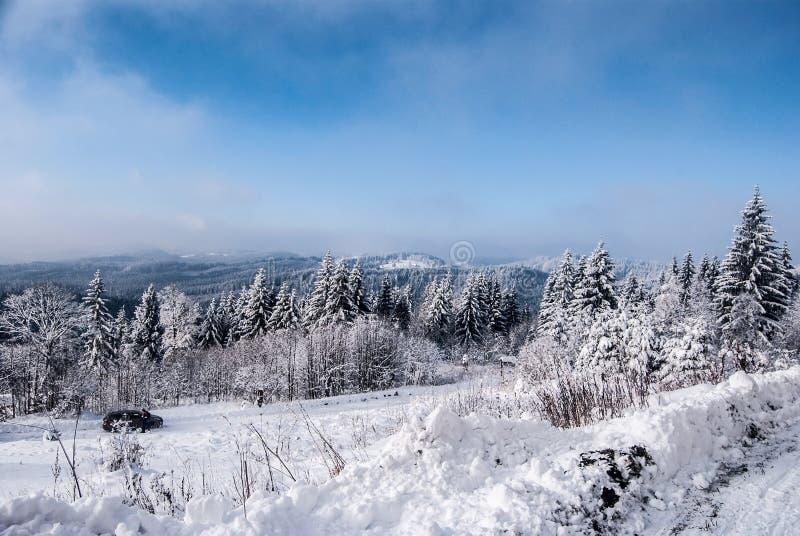 Τοπίο χειμερινών βουνών με το χιονισμένους δρόμο, το δάσος, τους λόφους, το χιόνι και το μπλε ουρανό με τα σύννεφα στοκ εικόνα