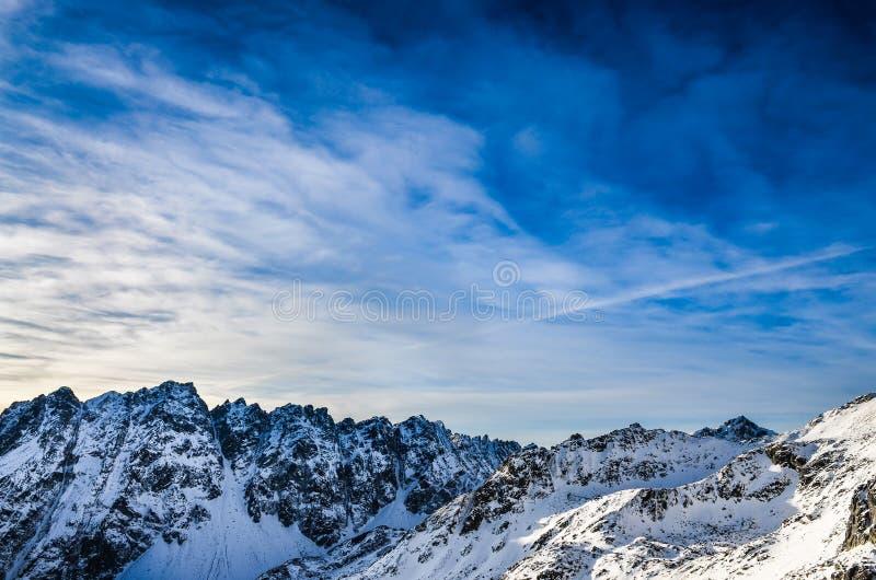 Τοπίο χειμερινών υψηλό βουνών Tatras με τον μπλε νεφελώδη ουρανό στοκ φωτογραφία