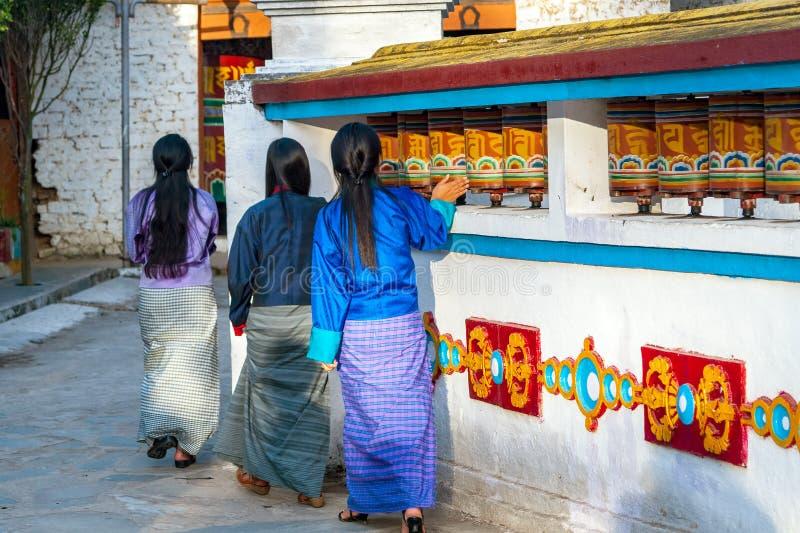 Τοπικές Bhutanese γυναίκες που γυρίζουν τις ρόδες προσευχής - Μπουτάν στοκ εικόνες με δικαίωμα ελεύθερης χρήσης