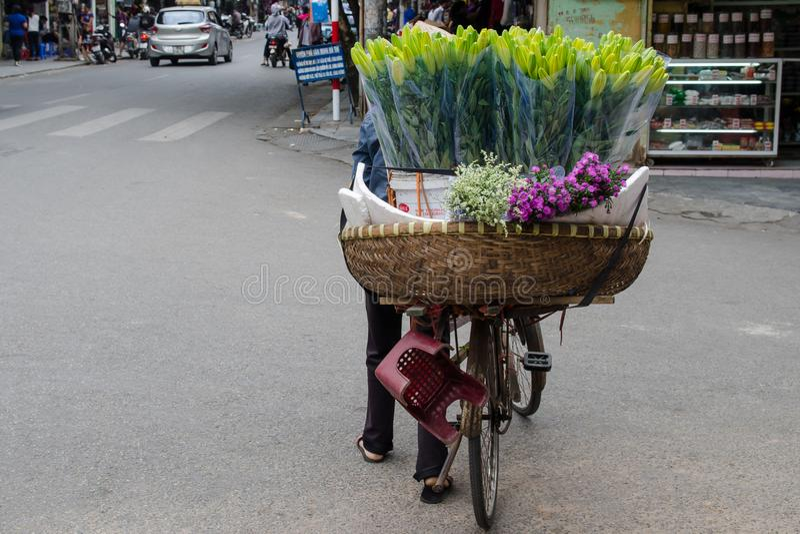 Τοπική καθημερινή ζωή της οδού στο Ανόι, Βιετνάμ Πλανόδιοι πωλητές που πωλούν τους διάφορους τύπους λουλουδιών από το ποδήλατό το στοκ εικόνες