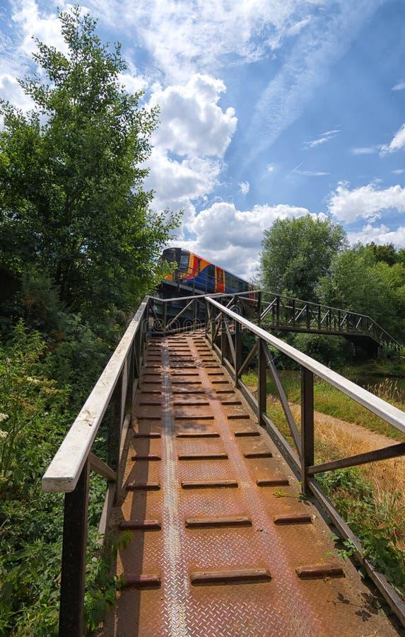 Τοπική κατηγορία 450 τραίνο που διασχίζει τη γέφυρα πέρα από τον ποταμό Wey, Surrey στοκ φωτογραφία