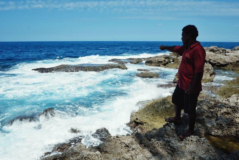 τοπικός του χωριού προϊστάμενος που δείχνει έναν ιερό βράχο στην τροπική νότια ακτή Ειρηνικών Ωκεανών με ζαλίζοντας seascape στοκ φωτογραφία
