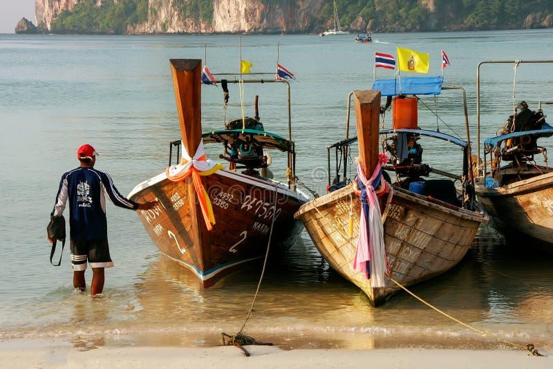 Τοπικό άτομο που υπερασπίζεται τις βάρκες longtail στην παραλία AO Loh Dalum στο pH στοκ εικόνα