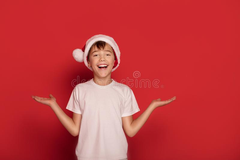Τοποθέτηση αγοριών χαμόγελου νέα ευτυχής στο καπέλο Άγιου Βασίλη στοκ εικόνες με δικαίωμα ελεύθερης χρήσης