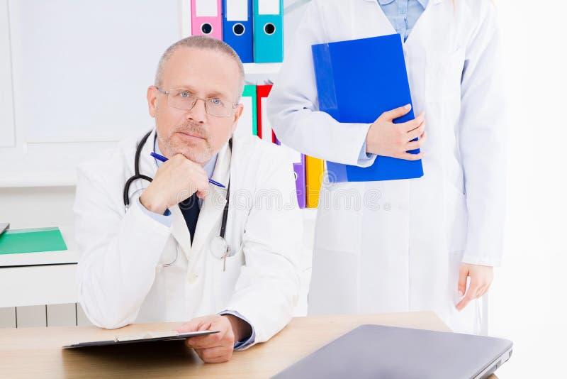 Τοποθέτηση γιατρών στην αρχή με το ιατρικό προσωπικό, φορά ένα στηθοσκόπιο Έννοια ποιοτικής ιατρικής Άτομο άσπρο σε ομοιόμορφο στοκ εικόνα με δικαίωμα ελεύθερης χρήσης
