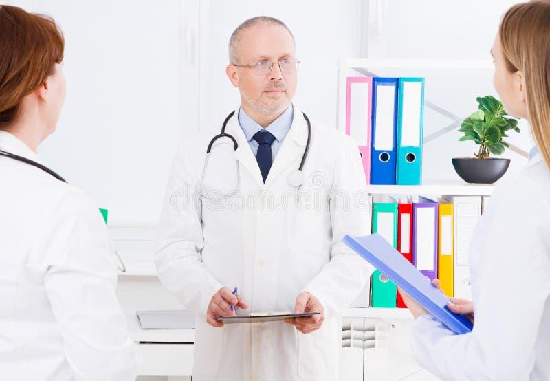 Τοποθέτηση γιατρών στην αρχή με το ιατρικό προσωπικό, φορά ένα στηθοσκόπιο Έννοια ποιοτικής ιατρικής Άτομο άσπρο σε ομοιόμορφο στοκ φωτογραφίες