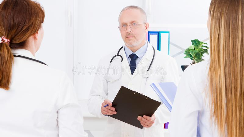 Τοποθέτηση γιατρών στην αρχή με το ιατρικό προσωπικό, φορά ένα στηθοσκόπιο Έννοια ποιοτικής ιατρικής Άτομο άσπρο σε ομοιόμορφο στοκ εικόνες