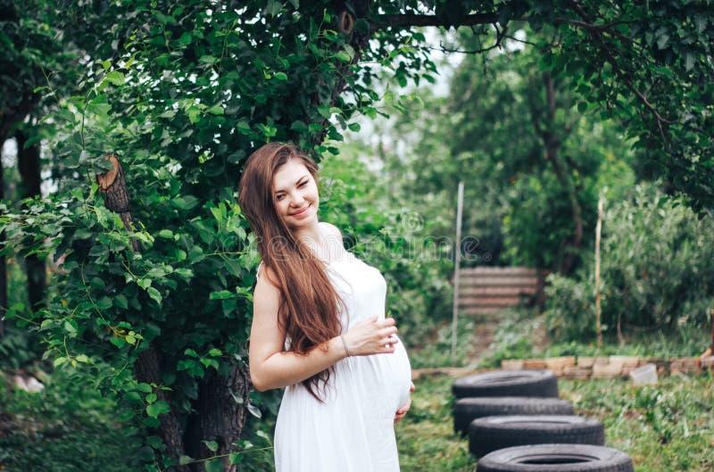 Τοποθέτηση εγκύων γυναικών σε έναν πράσινο κήπο μήλων στοκ φωτογραφίες