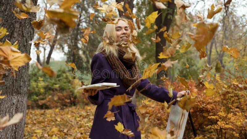 Τοποθέτηση καλλιτεχνών νέων κοριτσιών μεταξύ των μειωμένων φύλλων με easel στο πάρκο φθινοπώρου στοκ εικόνα με δικαίωμα ελεύθερης χρήσης