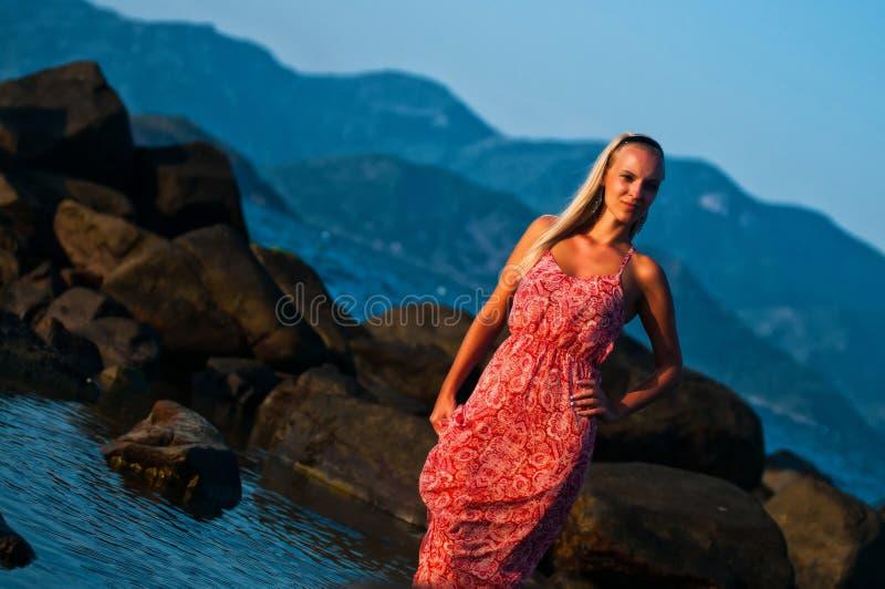 Τοποθέτηση κοριτσιών στο ηλιοβασίλεμα σε ένα υπόβαθρο των πετρών, των βουνών και της θάλασσας στοκ εικόνες
