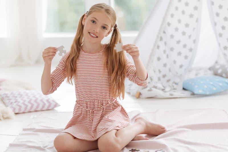 Τοποθέτηση κοριτσιών χαμόγελου με τα κομμάτια γρίφων στοκ εικόνες