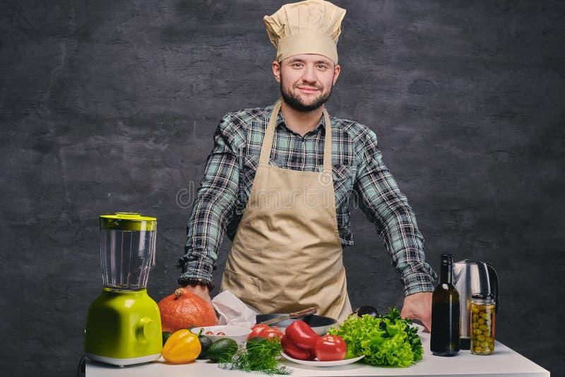 Τοποθέτηση μαγείρων αρχιμαγείρων κοντά στον πίνακα με πολλά φρέσκα λαχανικά στοκ εικόνα με δικαίωμα ελεύθερης χρήσης