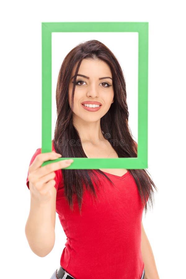 Τοποθέτηση νέων κοριτσιών πίσω από ένα πλαίσιο εικόνων στοκ εικόνες