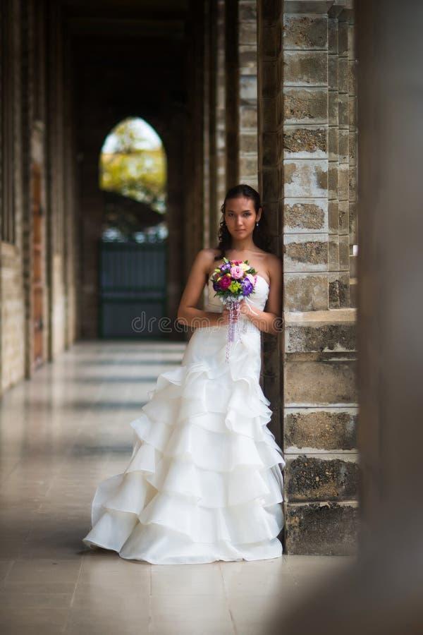 Τοποθέτηση νυφών στη στοά των τοίχων πετρών σε ένα όμορφο άσπρο γαμήλιο φόρεμα με μια ανθοδέσμη των λουλουδιών στοκ φωτογραφία με δικαίωμα ελεύθερης χρήσης