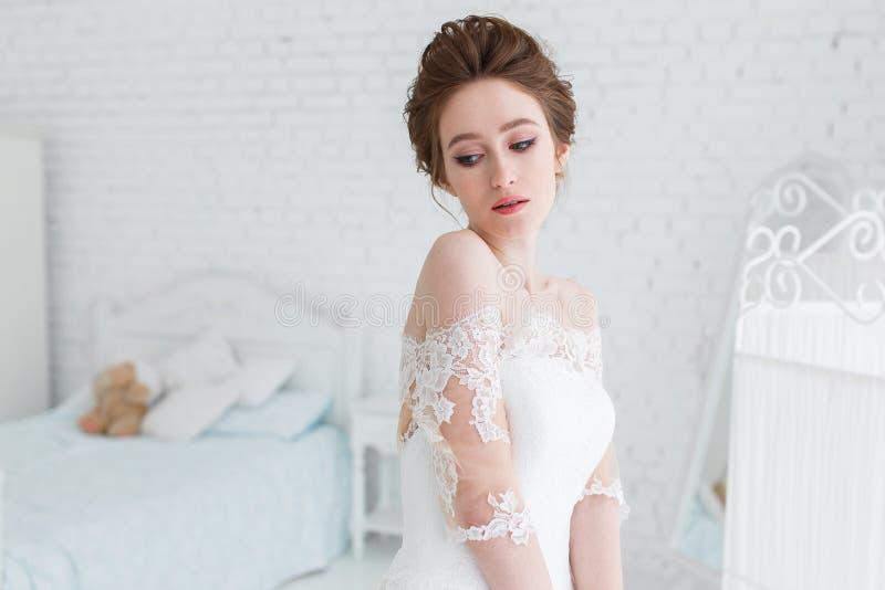 Τοποθέτηση νυφών στο γαμήλιο φόρεμα στο στούντιο σε ένα υπόβαθρο ενός τουβλότοιχος και ενός άσπρου κρεβατιού Οριζόντιο στενό πορτ στοκ εικόνα με δικαίωμα ελεύθερης χρήσης