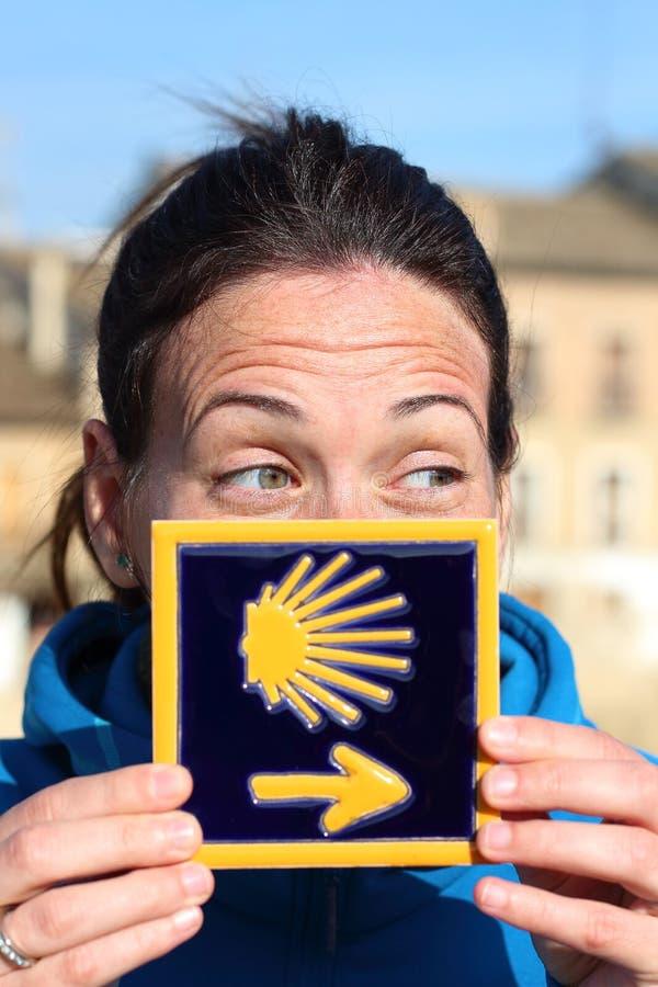 Τοποθέτηση πορτρέτου του νέου όμορφου θηλυκού προσκυνητή με το χαρακτηριστικό μπλε κεραμίδι Camino de Σαντιάγο στοκ εικόνες