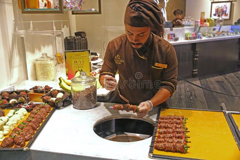 Τοποθέτηση της σοκολάτας σε ένα ραβδί με τα φρούτα στοκ εικόνα