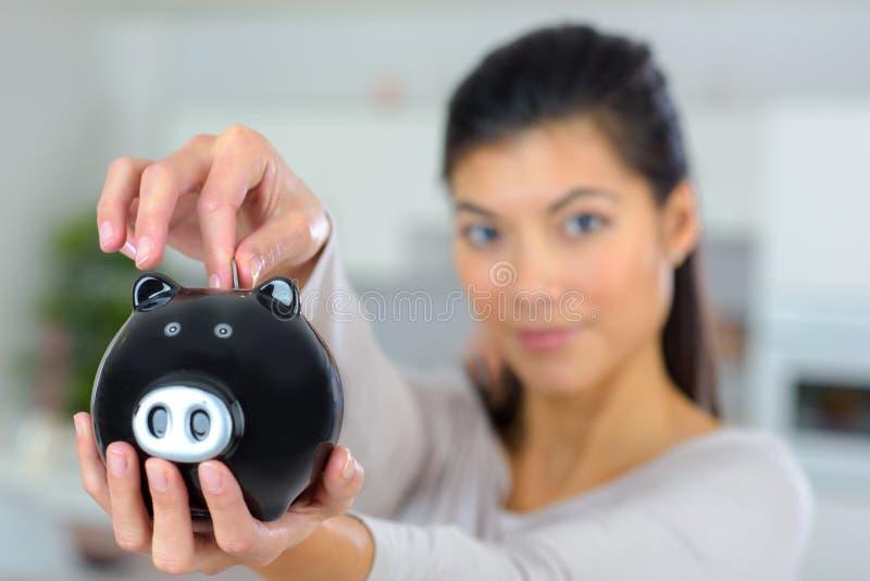 Τοποθέτηση του νομίσματος στη piggy τράπεζα στοκ εικόνα
