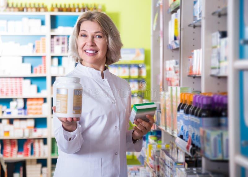 Τοποθέτηση φαρμακοποιών χαμόγελου θηλυκή στο φαρμακείο στοκ φωτογραφίες με δικαίωμα ελεύθερης χρήσης
