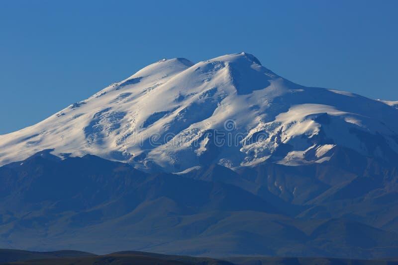 Τοποθετήστε Elbrus στην αυγή Άποψη των ηλιοφώτιστων κλίσεων του ηφαιστείου στοκ φωτογραφία με δικαίωμα ελεύθερης χρήσης