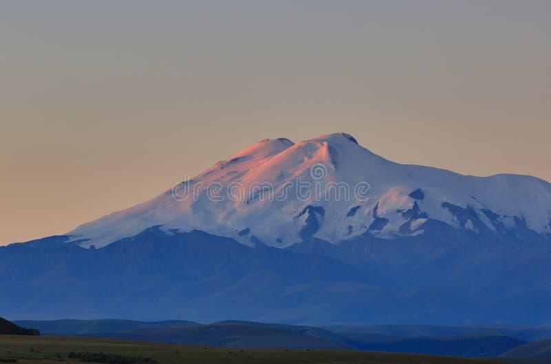 Τοποθετήστε Elbrus στην αυγή Άποψη των ηλιοφώτιστων κλίσεων του ηφαιστείου στοκ εικόνες