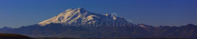 Τοποθετήστε Elbrus στην αυγή Πανοραμική άποψη των ηλιοφώτιστων κλίσεων στοκ εικόνες