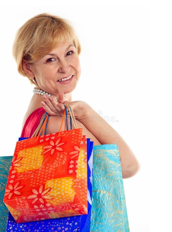 τοποθετεί τις γυναικείες ώριμες όμορφες αγορές μεταφοράς σε σάκκο στοκ εικόνα με δικαίωμα ελεύθερης χρήσης