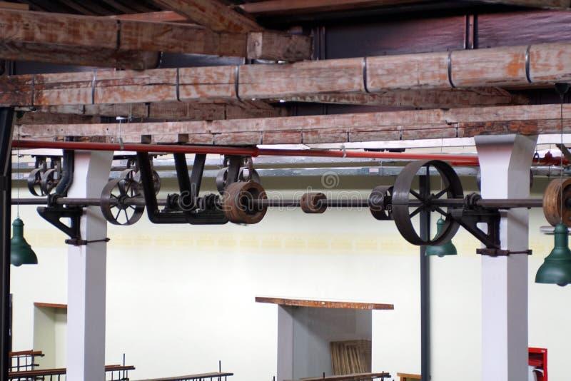 Τοποθετημένες ανώτατο όριο ζώνες και τροχαλίες σε ένα παλαιό εργοστάσιο επεξεργασίας βαμβακιού στοκ φωτογραφία με δικαίωμα ελεύθερης χρήσης
