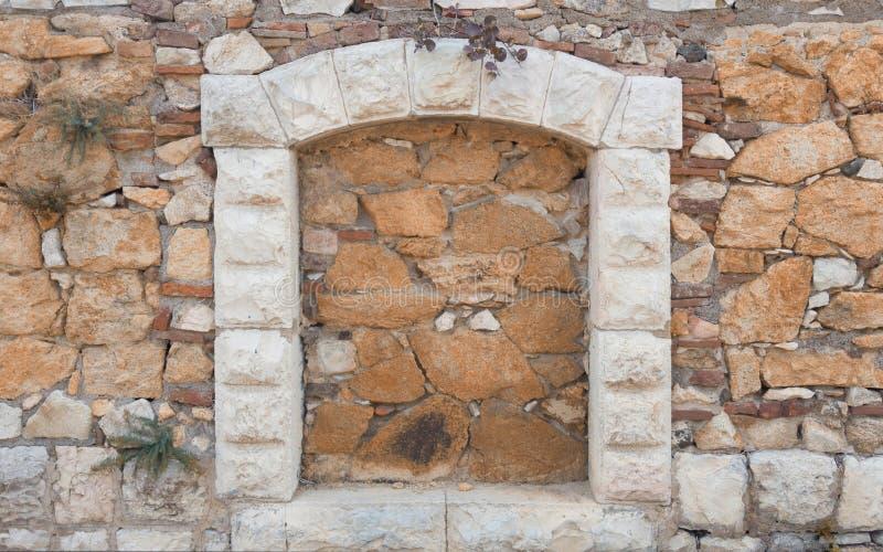 Τοποθετημένο σχηματισμένο αψίδα παράθυρο στον τοίχο πετρών του σπιτιού στοκ φωτογραφίες