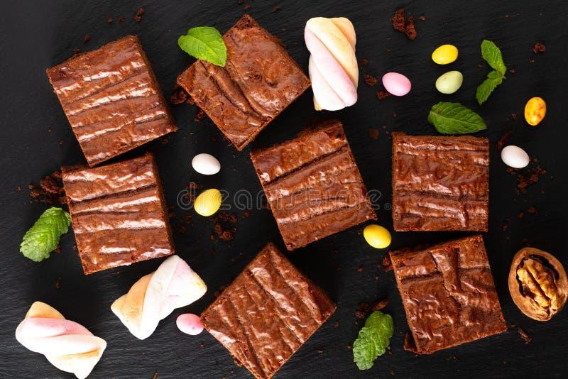 Τοπ άποψη έννοιας αρτοποιείων τροφίμων η σπιτική οργανικού Brownies διακοσμεί από την καραμέλα στο μαύρο πίνακα πλακών στοκ φωτογραφία