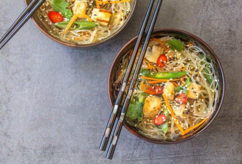 Τοπ άποψη δύο ασιατικών πιάτων με ένα vegan πιάτο των νουντλς γυαλιού, tofu και των φρέσκων λαχανικών στοκ εικόνα με δικαίωμα ελεύθερης χρήσης