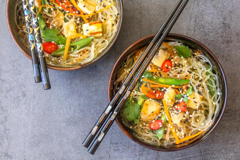 Τοπ άποψη δύο ασιατικών πιάτων με ένα vegan πιάτο των νουντλς γυαλιού, tofu και των φρέσκων λαχανικών στοκ εικόνες με δικαίωμα ελεύθερης χρήσης