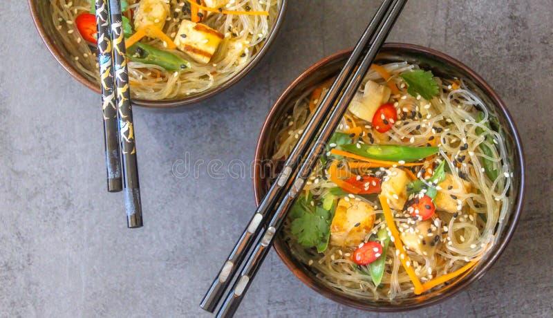 Τοπ άποψη δύο ασιατικών πιάτων με ένα vegan πιάτο των νουντλς γυαλιού, tofu και των φρέσκων λαχανικών στοκ εικόνα