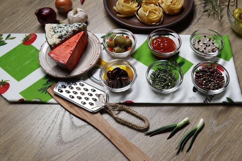 Τοπ άποψη δύο τύπων τυριών και ελιών στο υπόβαθρο των ζυμαρικών, του κρεμμυδιού, του σκόρδου και του πιπεριού σε μια πετσέτα στοκ εικόνες