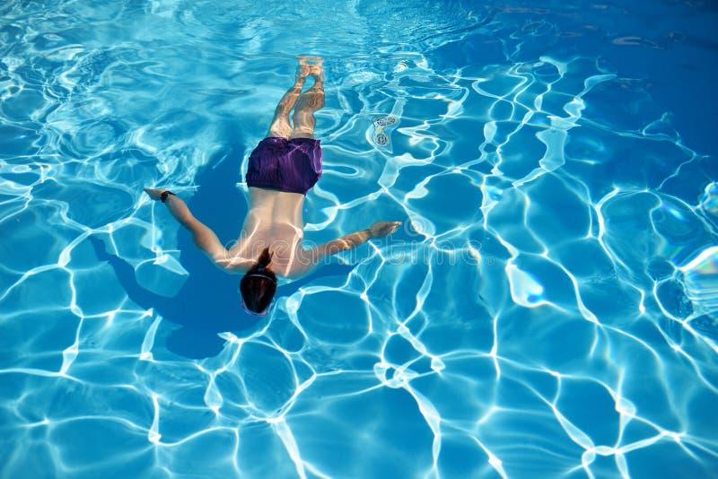 Τοπ άποψη ενός ατόμου που κολυμπά σε μια πισίνα την ηλιόλουστη θερινή ημέρα στοκ εικόνες