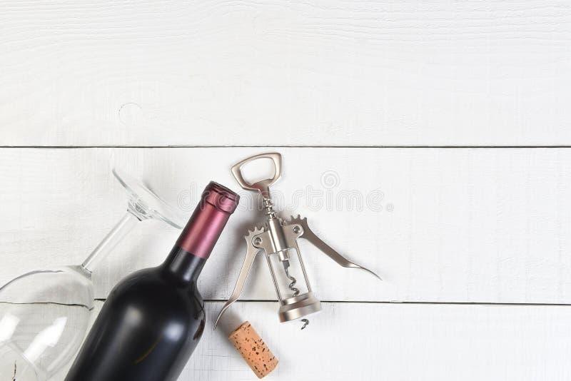 Τοπ άποψη ενός γυαλιού μπουκαλιών κρασιού και ενός ανοιχτήρι σε έναν άσπρο ξύλινο πίνακα στοκ εικόνα