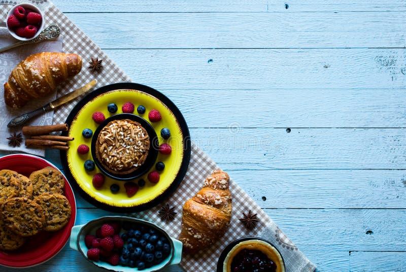 Τοπ άποψη ενός ξύλινου επιτραπέζιου συνόλου των κέικ, φρούτα, καφές, μπισκότα στοκ εικόνες