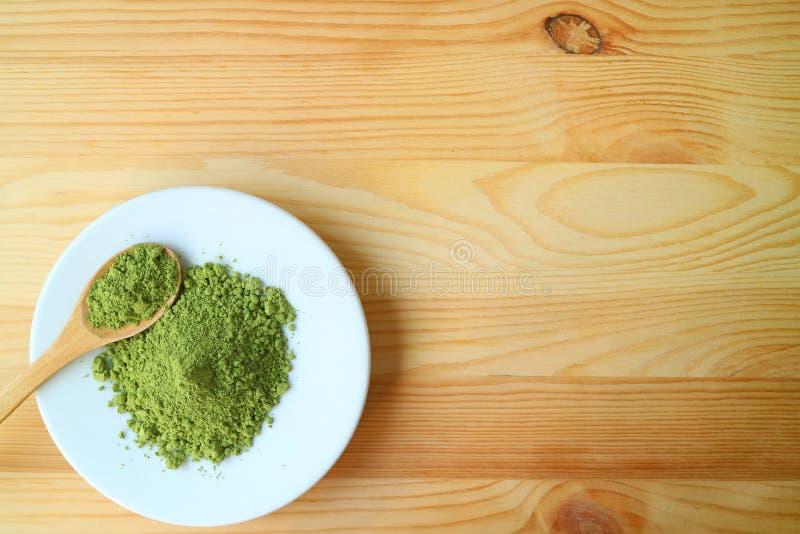 Τοπ άποψη ενός πιάτου της πράσινης σκόνης τσαγιού Matcha με ένα ξύλινο κουτάλι τσαγιού στον ξύλινο πίνακα στοκ φωτογραφία