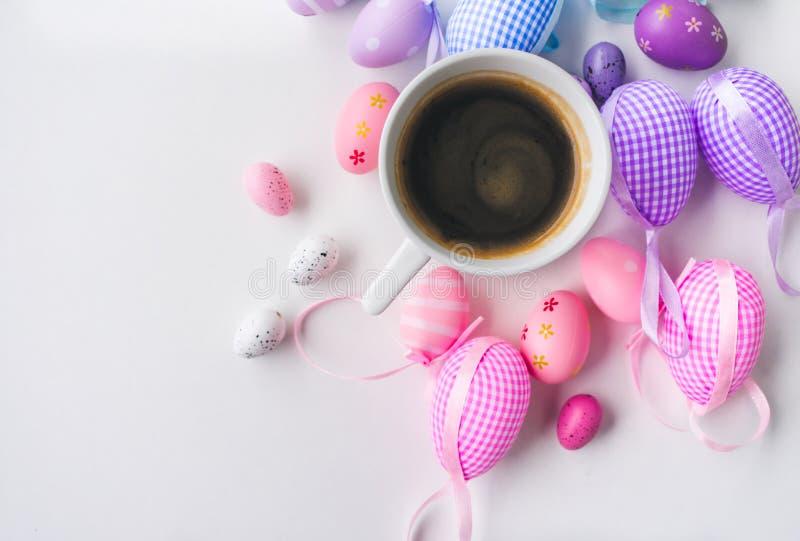 Τοπ άποψη ενός φλιτζανιού του καφέ και ζωηρόχρωμων διακοσμήσεων αυγών Πάσχας στο άσπρο υπόβαθρο στοκ φωτογραφία με δικαίωμα ελεύθερης χρήσης