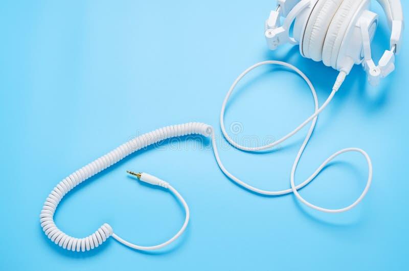 Τοπ άποψη επάνω στις συσκευές στο μπλε υπόβαθρο, η σύνθεση των άσπρων ακουστικών και των καλωδίων με μορφή μιας καρδιάς στοκ εικόνα