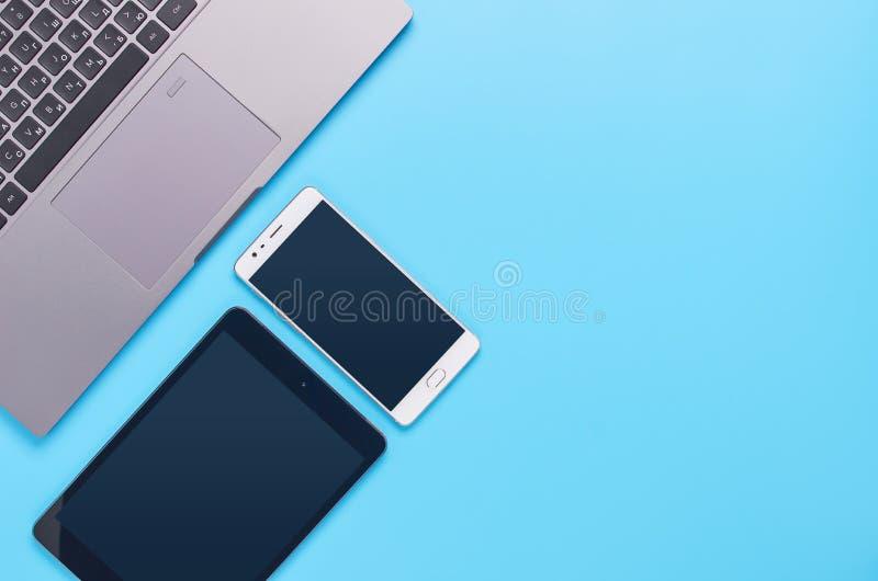 Τοπ άποψη επάνω στις συσκευές στο μπλε υπόβαθρο, τη σύνθεση ενός lap-top, τα άσπρα ακουστικά, το τηλέφωνο, το γυαλί με ένα ποτό κ στοκ εικόνες με δικαίωμα ελεύθερης χρήσης