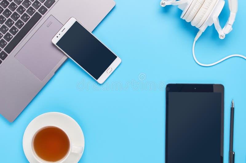 Τοπ άποψη επάνω στις συσκευές στο μπλε υπόβαθρο, τη σύνθεση ενός lap-top, τα άσπρα ακουστικά, το τηλέφωνο, το γυαλί με ένα ποτό κ στοκ εικόνα με δικαίωμα ελεύθερης χρήσης