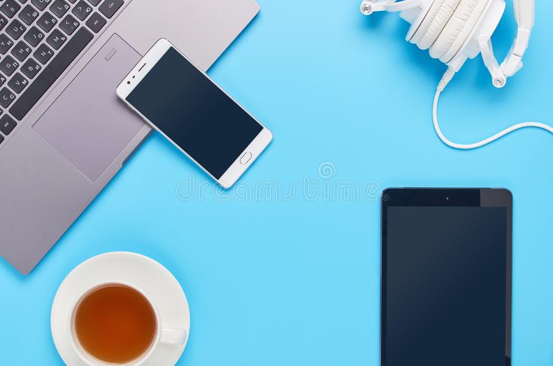 Τοπ άποψη επάνω στις συσκευές στο μπλε υπόβαθρο, τη σύνθεση ενός lap-top, τα άσπρα ακουστικά, το τηλέφωνο, το γυαλί με ένα ποτό κ στοκ φωτογραφία
