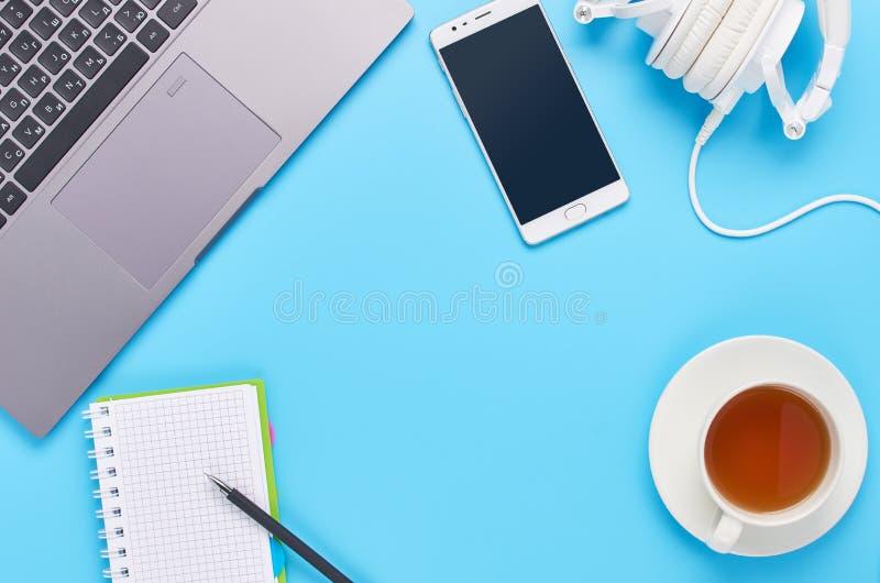 Τοπ άποψη επάνω στις συσκευές στο μπλε υπόβαθρο, τη σύνθεση ενός lap-top, τα άσπρα ακουστικά, το τηλέφωνο, το γυαλί με ένα ποτό κ στοκ εικόνες