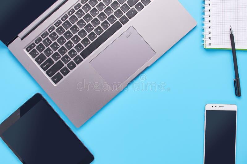 Τοπ άποψη επάνω στις συσκευές στο μπλε υπόβαθρο, τη σύνθεση ενός lap-top, τα άσπρα ακουστικά, το τηλέφωνο, το γυαλί με ένα ποτό κ στοκ εικόνα