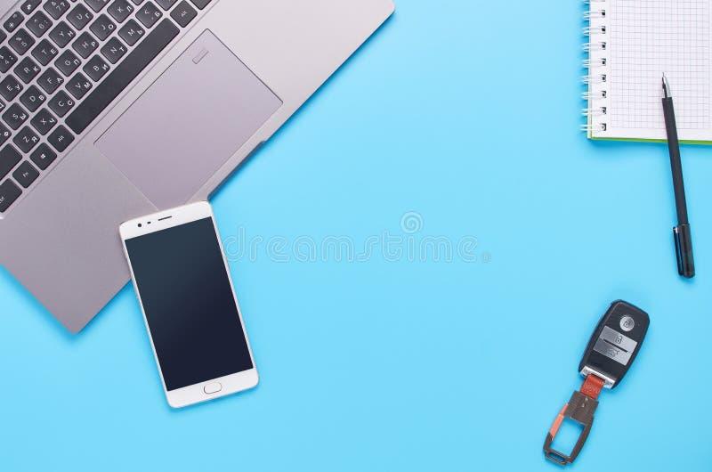 Τοπ άποψη επάνω στις συσκευές στο μπλε υπόβαθρο, τη σύνθεση ενός lap-top, τα άσπρα ακουστικά, το τηλέφωνο, το γυαλί με ένα ποτό κ στοκ φωτογραφία με δικαίωμα ελεύθερης χρήσης