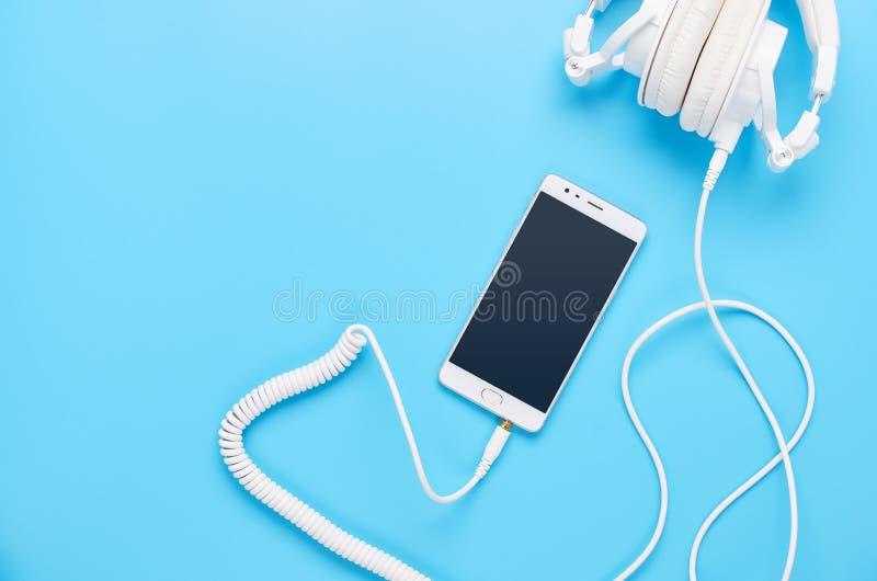 Τοπ άποψη επάνω στις συσκευές στο μπλε υπόβαθρο, τη σύνθεση των άσπρων ακουστικών και το τηλέφωνο στοκ φωτογραφία