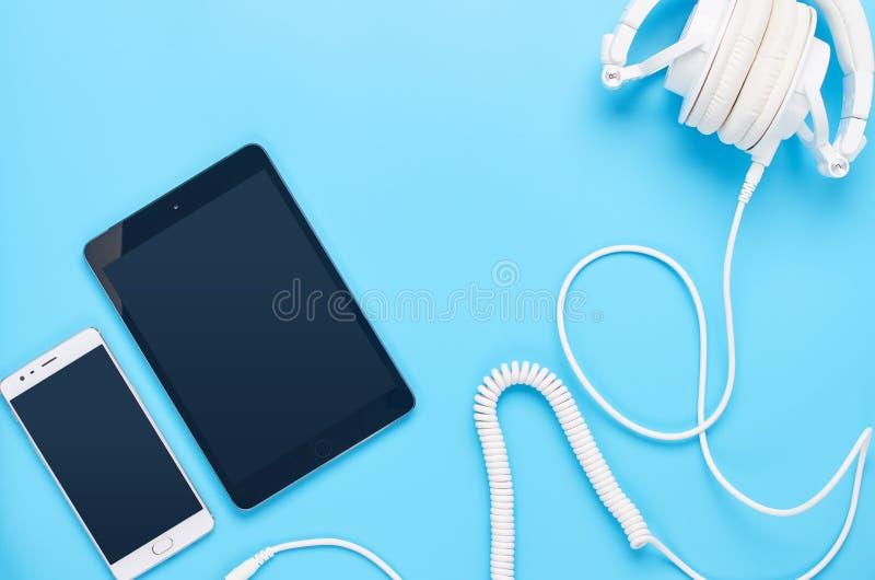 Τοπ άποψη επάνω στις συσκευές στο μπλε υπόβαθρο, τη σύνθεση των άσπρων ακουστικών, την ταμπλέτα και το τηλέφωνο στοκ φωτογραφία