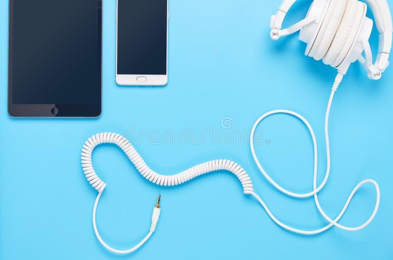 Τοπ άποψη επάνω στις συσκευές στο μπλε υπόβαθρο, τη σύνθεση των άσπρων ακουστικών, την ταμπλέτα και το τηλέφωνο στοκ εικόνες